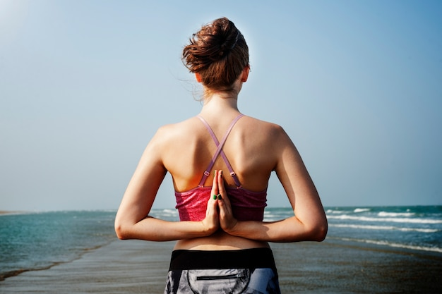 Woman doing reverse namaste yoga pose at the beach
