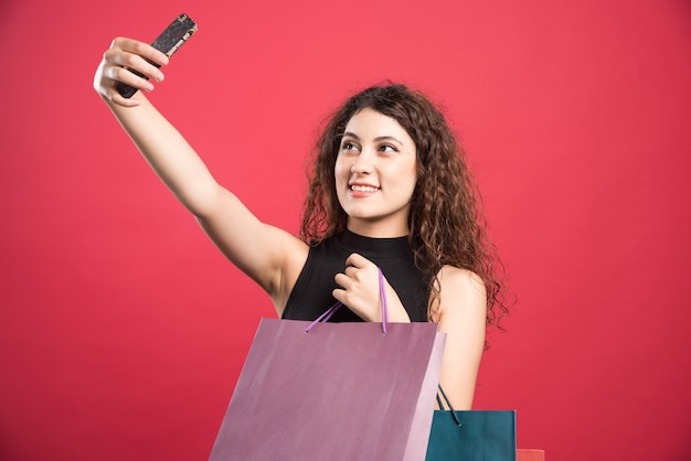 Woman doing selfie with bags on red .