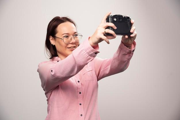 Donna che fa un selfie con una macchina fotografica su un bianco. foto di alta qualità