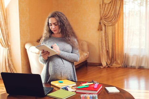 온라인 쇼핑을 하는 여자. 임신, 작업 및 쇼핑 개념입니다.