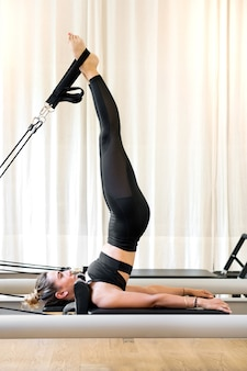 Woman doing short spine pilates exercise