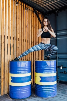 Woman doing side lunges on barrels