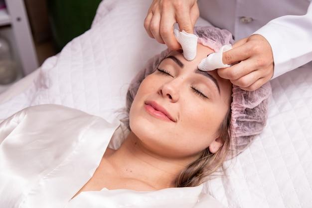Женщина делает чистку кожи в клинике косметолога. очистка кожи. удаление прыщиков с лица