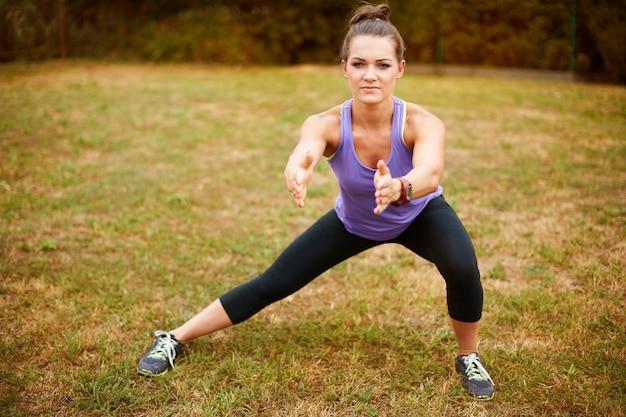 Женщина делает упражнения в парке