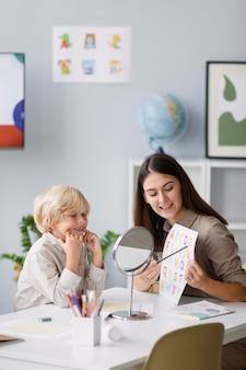 그녀의 클리닉에서 어린 소년과 언어 치료를 하는 여성