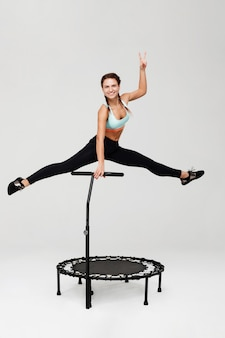 Woman doing split jumping up showing peace sign smiling cheerfully
