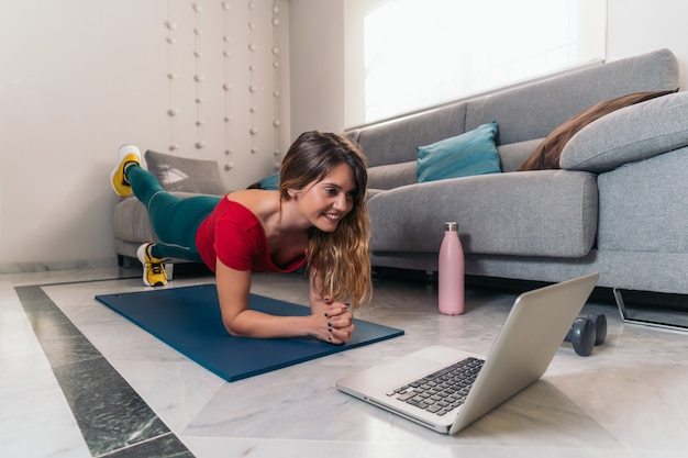 Woman doing sports on a mat following online classes with laptop at home