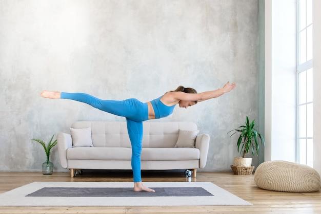 Женщина занимается спортивной йогой, стоя на коврике дома