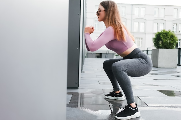 Woman doing squats and stretches in the city