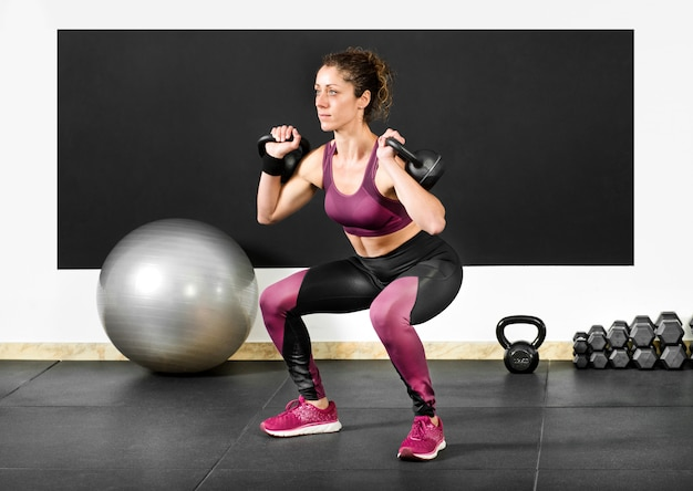 Woman doing squats with kettlebells