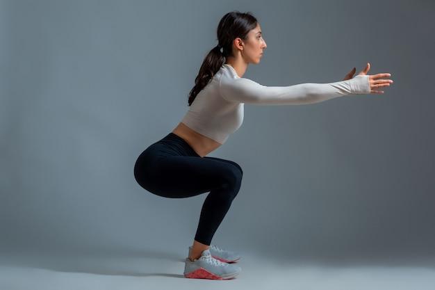 Женщина делает приседания с вытянутыми руками на серой стене