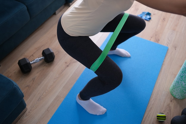 Woman doing squats with rubber band at home