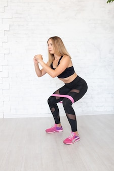 Woman doing squats with a rubber band
