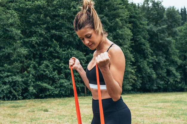 Woman doing strength training with a rubber band in the middle of a forest