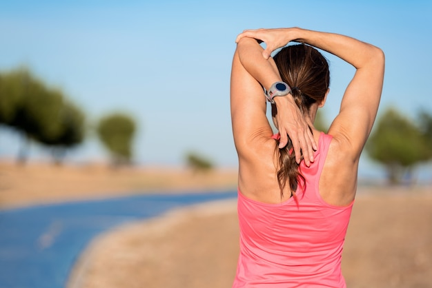 Woman doing stretching exercise for arms, sport background.