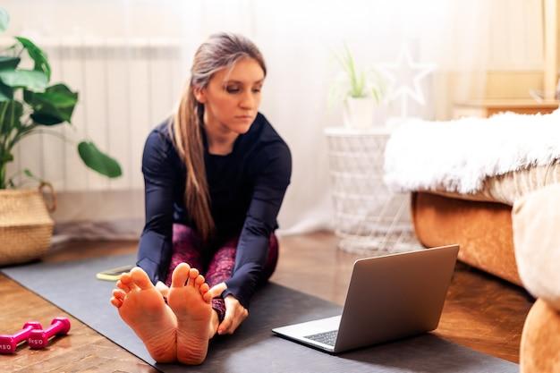 Женщина делает упражнения на растяжку дома Premium Фотографии