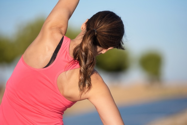 Woman doing stretching exercise for back, sport background.