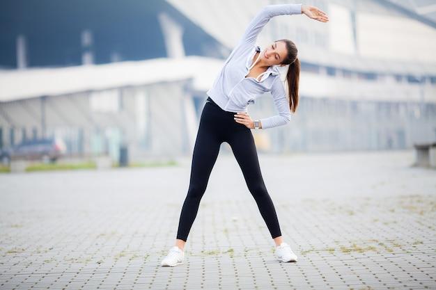 Женщина делает упражнения на растяжку на стадионе