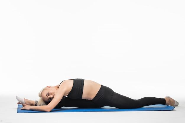 Женщина делает упражнения на растяжку на полу в студии на белом