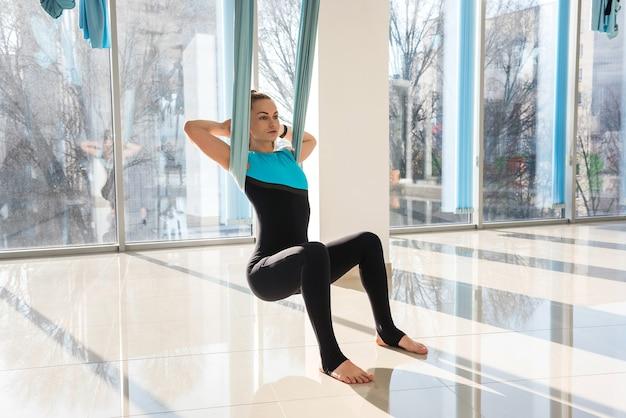 Женщина делает упражнения на растяжку, используя муху-йогу в фитнес-тренировках. здоровье, концепция йоги летать.