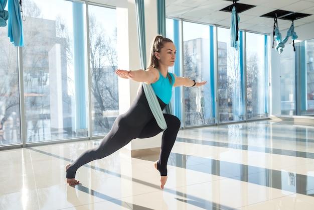 フィットネストレーニングでフライヨガを使用してストレッチ体操をしている女性。健康、フライヨガのコンセプト。
