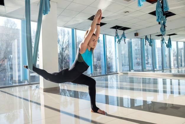 Женщина делает упражнения на растяжку, используя летательную йогу в фитнес-тренировках