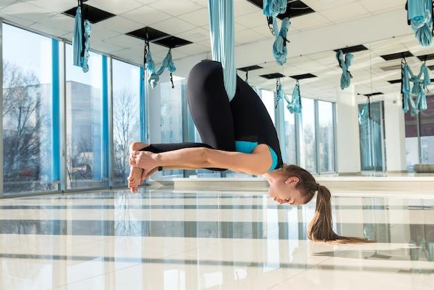 Женщина делает упражнения на растяжку с помощью мух-йоги