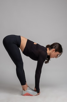 Woman doing stretching forward bends on grey wall