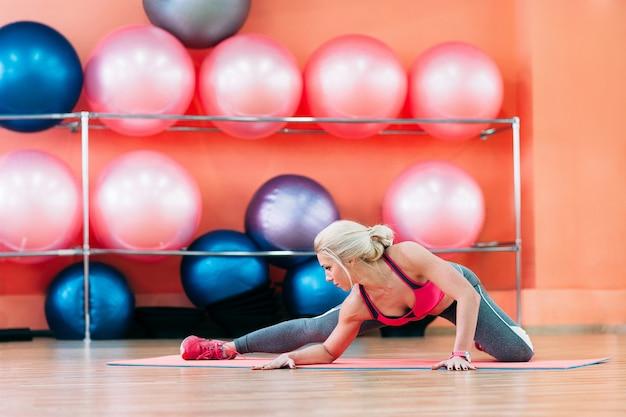 Женщина делает растяжку в фитнес-студии