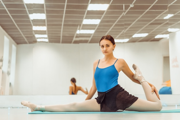 Woman doing stretching on the mat in the hall sitting on the twine