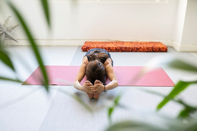 Woman doing stretching on a mat in a room