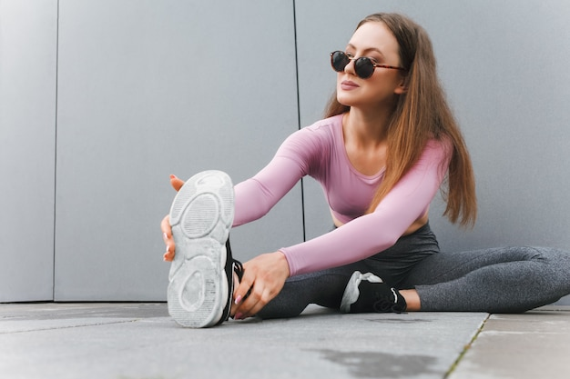 Woman doing stretching on wall background