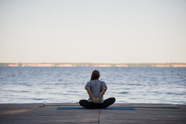 海や湖の近くの桟橋で午前中にストレッチヨガの練習をしている女性