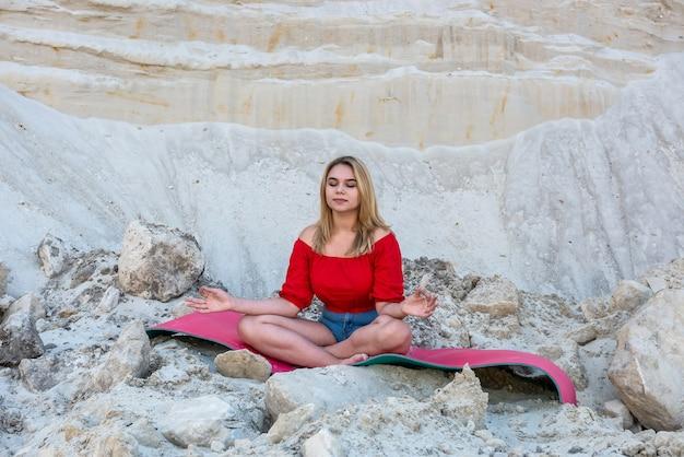 自然砂採石場でマットの上でストレッチヨガの練習をしている女性。瞑想