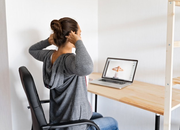 Woman doing stretching yoga at her office by online sport video.