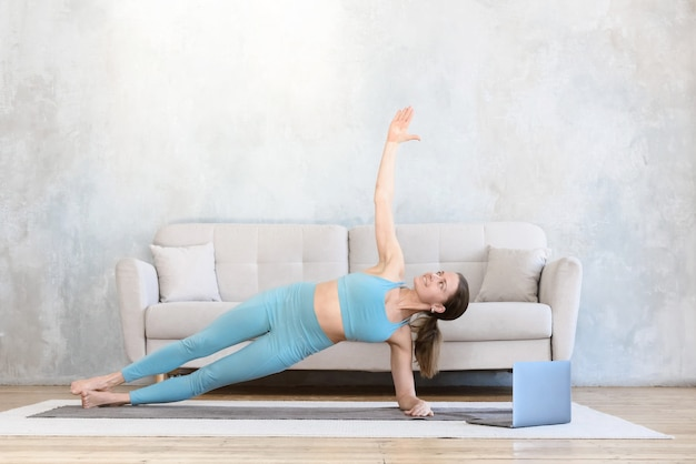 Woman doing stretching yoga at home using laptop side plank pose