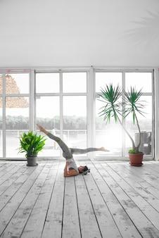 Женщина делает позу стойки на плечах во время занятий йогой в помещении