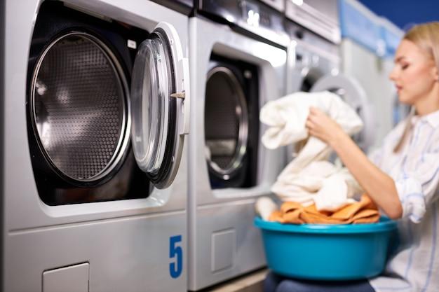 Женщина занимается повседневными делами - стиркой. женщина сложила чистую одежду в корзине для белья, вид сбоку. уборка, стирка концепции. сосредоточиться на стиральной машине