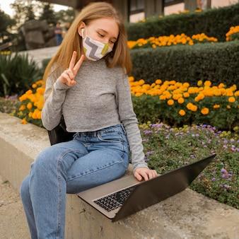 Женщина делает знак мира во время видеозвонка на ноутбуке