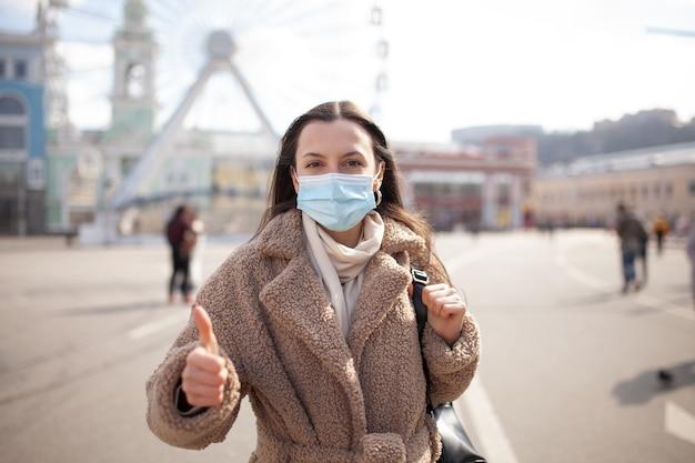 Женщина делает жест большие пальцы руки в защитной маске молодая женщина в медицинской стерильной защитной маске на лице