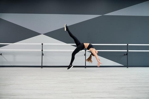 Woman doing wheel jump in dance hall