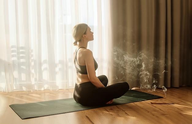 Женщина занимается йогой и медитирует с горящими ароматными благовониями, дымчатая палочка практика йоги дома