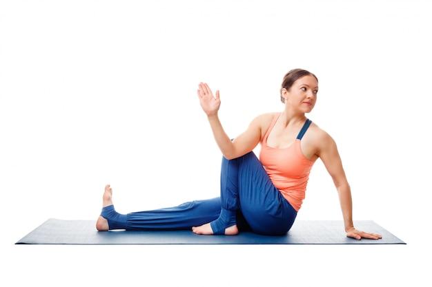 Woman doing yoga asana ardha matsyendrasana isolated on white