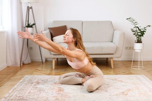 居間で自宅でヨガをしている女性