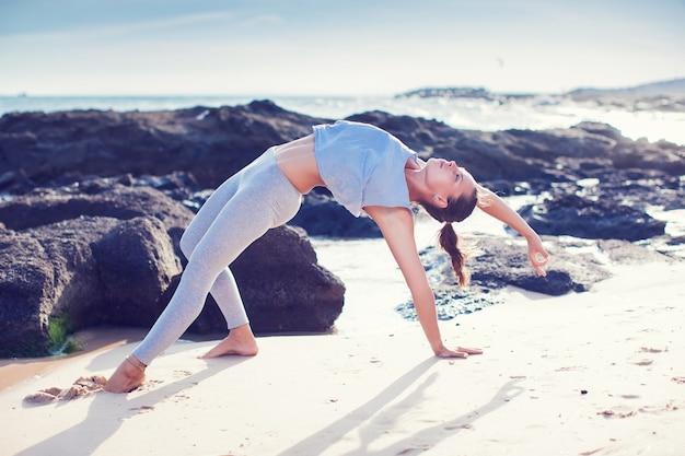 Woman doing yoga on the beach