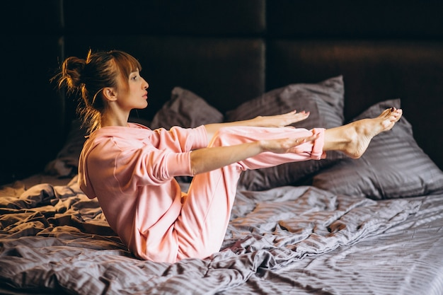 Woman doing yoga in bed