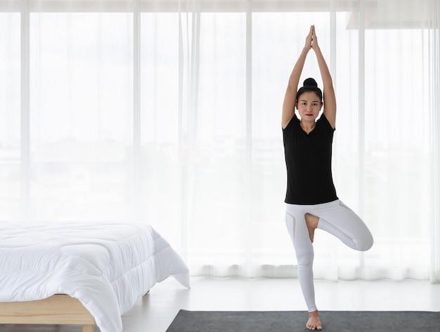 朝起きた後、自宅でヨガのエクササイズをし、木のポーズでストレッチしたり、白い寝室でvrikshasanasvanasanaをしたりする女性。ヘルスケアの概念。