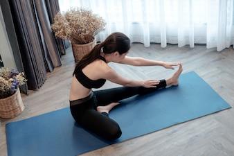 ヨガをする家庭で運動する女性。
