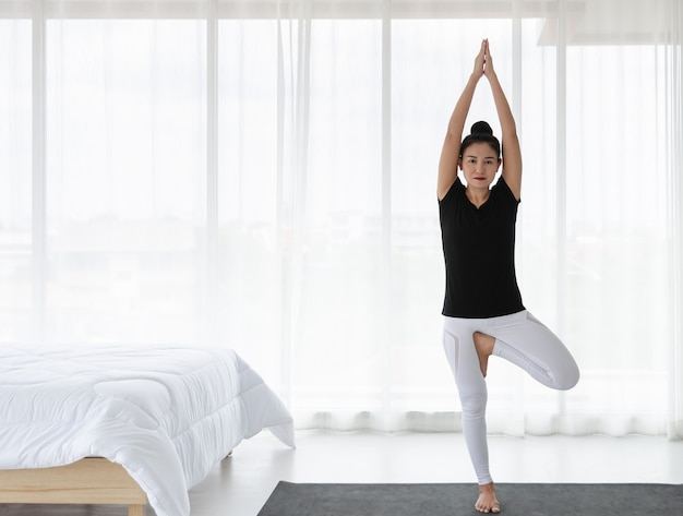 Woman doing yoga exercise at home, stretching in tree pose or vrikshasana svanasana in white bedroom after wake up in the morning. healthcare concept.