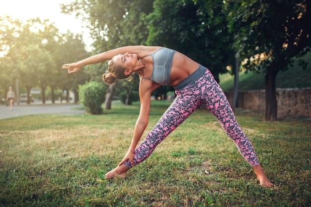 Женщина делает упражнения йоги в летнем парке